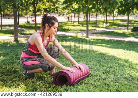 Young Caucasian Woman Unfolding A Yoga Matt On The Grass Of A Green Park. She Is Wearing Pink And Gr