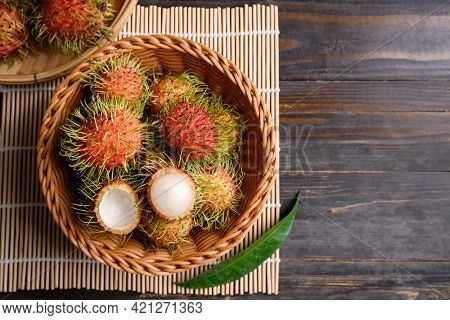 Ripe Rambutan Fruit In A Basket On Wooden Background, Rambutan Is Tropical Fruit And Native Southeas