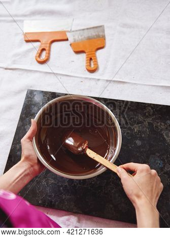 Top View Of Chocolatier Mixing Melted Chocolate Mass With Wooden Spoon, Scrapers Lying Near Marble S