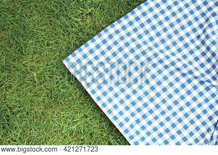 Blue Checkered Picnic Cloth On Green Grass Top View. Checkered Towel Country Design Backdrop. Food A
