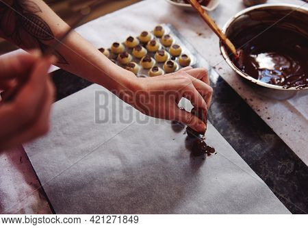 Confectioner Sprinkling Cocoa Powder On A Handmade Truffle Dipped In A Melted Chocolate Mass. Manufa