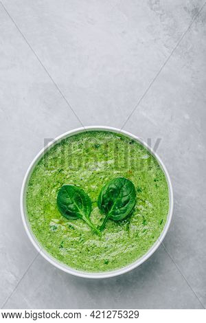 Green Creamy Spinach Soup On A Gray Concrete Background. Healthy Food And Diet. Top View.