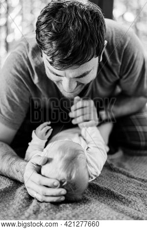 Dad Put One Hand On The Babys Head, And The Other Holds His Hand. Baby And Dad Lie On The Rug On The