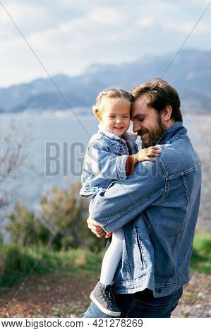 Happy Dad Holds In His Arms A Smiling Little Girl Standing On The Shore Against The Background Of Th