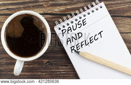 Pause And Reflect Text On Notebook With Coffee On The Wooden Background