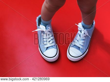 A Small Child In The Sneakers Of A Large Adult. The Concept Of Growing Up, The Continuity Of Generat