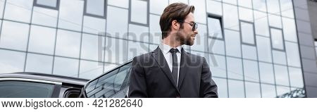 Side View Of Bearded Bodyguard In Suit Near Car And Modern Building, Banner.