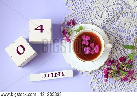 Calendar For June 4: Cubes With The Numbers 0 And 4, The Name Of The Month Of June In English, A Cup