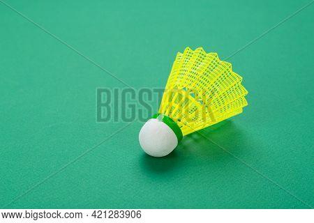 Badminton Ball Or Shuttlecock On Green Background.   Popular Indoor Sport Concept.