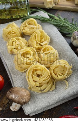 Raw Pasta Tagliatelle With Fresh Tomatoes, Peppers, Asparagus Beans, Spices And Cheese On Wood Backg