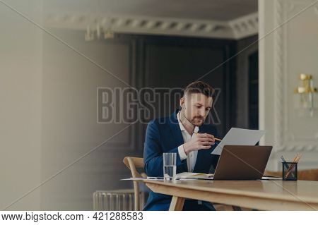 Handsome Business Executive In Dark Blue Suit Sitting At His Work Desk In Light Colored Office Worki