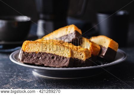 Sliced sponge dessert. Sweet sponge cake with chocolate on black table.