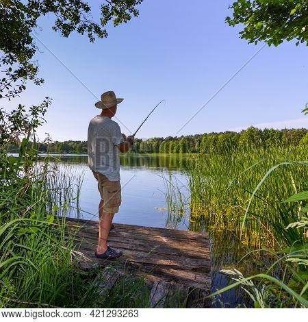 Angler Catching The Fish In The Lake Durring Summer Day