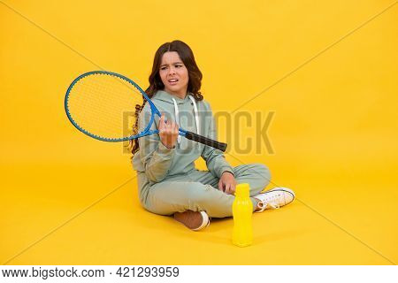 Unhappy Kid Sit With Racket Water Bottle. Child With Tennis Racquet. Teen Girl Going To Drink Water