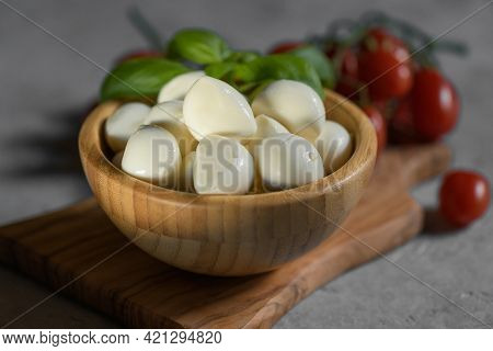 Close Up Of Fresh Apulian Mozzarella Cheese In A Wooden Bowl With Fresh Leaf Of Basil, Close Up And