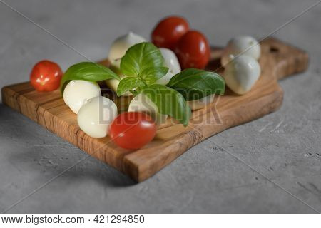 Close Up Of Fresh Apulian Mozzarella Cheese On A Wooden Cutting Board With Fresh Leaf Of Basil, Clos