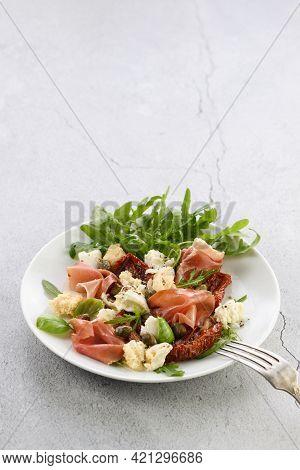 Salad Arugula, Parma Ham With Sun-dried Tomatoes, Mozzarella Slices, Croutons, Capers, Seasoned Oil