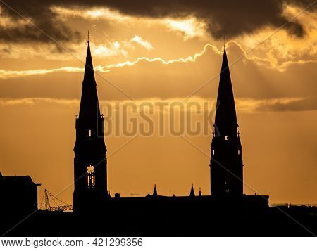 Two Church Spires Silhouette On A Golden Sunset, Ireland