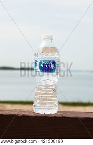 Bottle with Nestle Pure Life water outside in sunny day on waterfront