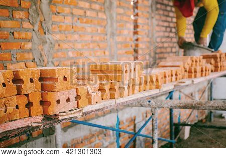 Focus On The Orange Bricks Within The Construction Site Where Construction Workers Are Working. The