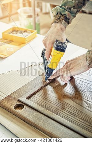 Skilled Carpenter Assembles Wooden Door For Kitchen Cabinet Fixing Glazing Bead With Pins From Pneum