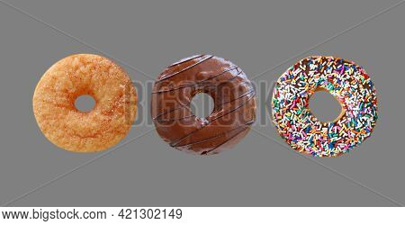 Three Of Delectable Assorted Donuts Isolated On Gray Background