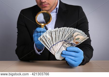 Expert Authenticating 100 Dollar Banknotes With Magnifying Glass At Table On Light Grey Background,