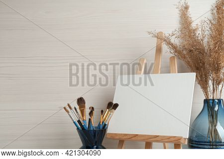 Easel With Blank Canvas And Brushes In Studio. Space For Text