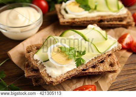 Fresh Rye Crispbreads With Quail Egg, Cream Cheese And Cucumber Slices On Wooden Table, Closeup