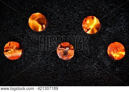 Fiery Circles On A Black Background On The Barbeque, Fiery Flame Through The Wall Of The Barbeque