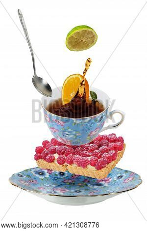 Levitating Teacup With Saucer And Raspberry Tart. Isolated On A White Background