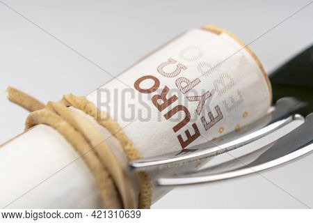 Rolled Up Rubber Band Bills On A Dessert Fork. Close Up. Macro Shot. Abundance And Corruption Concep