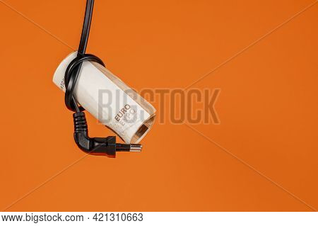 Euro Bills Are Tied In A Knot By A Black Electric Cable With A Plug On A Colored Orange Background.