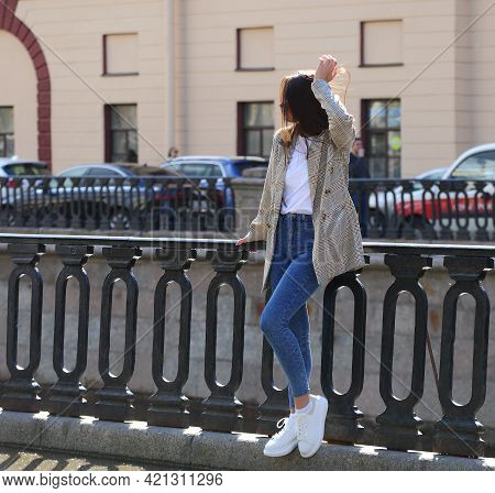 A Girl In Jeans, White Sneakers And A Checkered Jacket At The Cast-iron Fence Of The Embankment, Gri