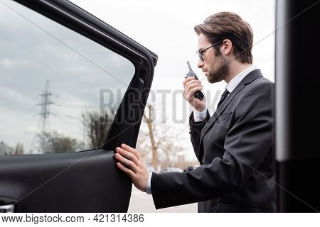 Side View Of Bearded Bodyguard In Suit And Sunglasses Using Walkie Talkie Near Modern Car.