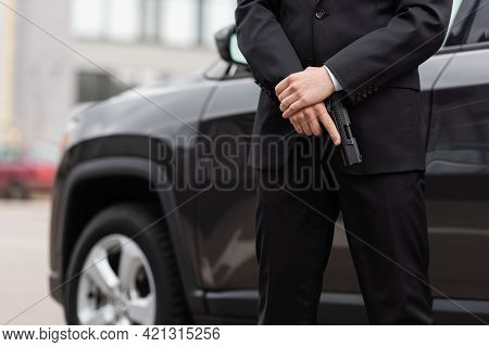 Cropped View Of Bodyguard In Suit Holding Gun Near Blurred Modern Auto.