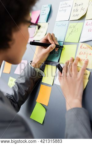 Marker In Hand Of African American Manager Near Colorful Sticky Notes On Board.