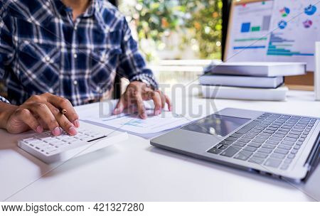 Business Accounting Concepts. Businessman Or Accountant Using Calculator To Calculate Business Repor