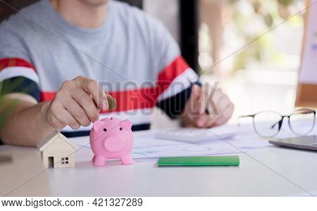 Close Up Young Man Putting Coin In Piggy Bank And Calculate Savings Money Plan To Buy Property, Hous