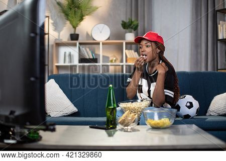 Young Female Fan Watching Soccer Match On Tv While Staying Alone At Home. Pretty Woman Eating Popcor