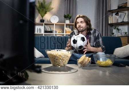 Male Sport Fan With Ball In Hands Sitting On Couch And Watching Soccer Match On Tv. Caucasian Guy St