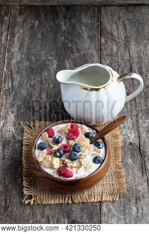 Rice  And Wholewheat Cereal Flakes With Dried And Fresh Berries On Wooden Table
