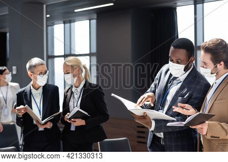 African American Businessman Pointing At Documents During Conversation With Colleague.