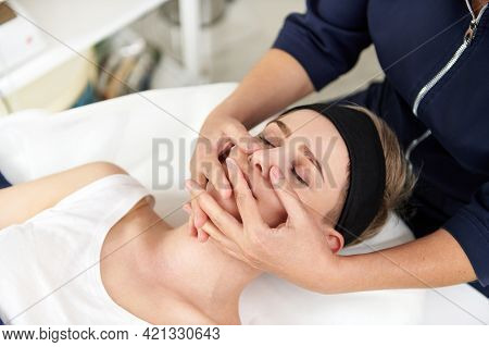 Close Up Portrait Of Aesthetician Hands Doing Professional Rejuvenating Face Massage To Young Blonde