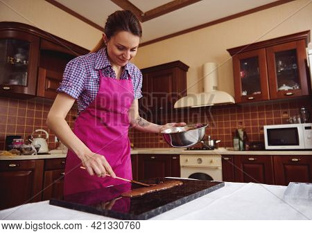 Young Woman Chocolatier Holding Cake Scrapers Near Melted Chocolate On Marble Surface On The Backgro
