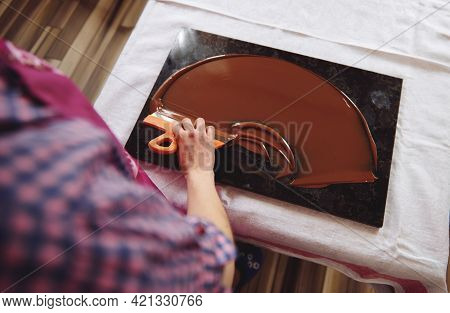 Top View Of Chocolatier Holding Cake Scraber And Cooling Melted Chocolate Mass On A Marble Table. Cl