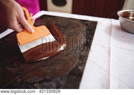 Confectioner Working On Tempering Melted Chocolate Mass On A Marble Surface. Manufacturing Chocolate