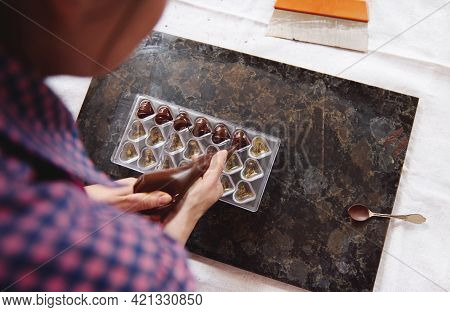 Chocolatier Squeezing Liquid Warm Chocolate Mass From Confectionery Bag Into Candy Molds. Process Ma