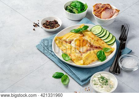 Delicious Breakfast With Pancake, Egg, Ham And Cheese On A Gray Background. Breton Galette. Side Vie