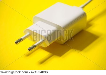 White Charging 220 Volts For A Phone With A Usb Connector On A Yellow Background